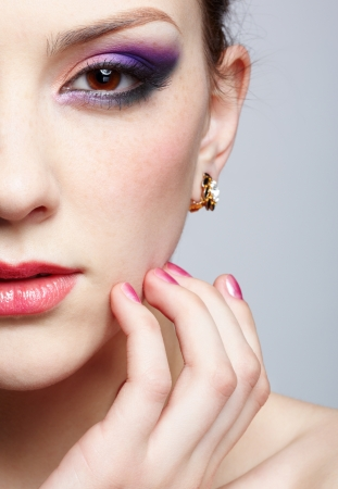 close-up half-face portrait of young beautiful woman with violet eye shadow touching her face with manicured fingers