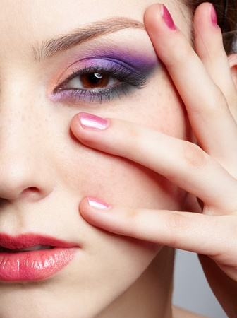 close-up half-face portrait of young beautiful woman with violet eye shadow touching her face with manicured hand