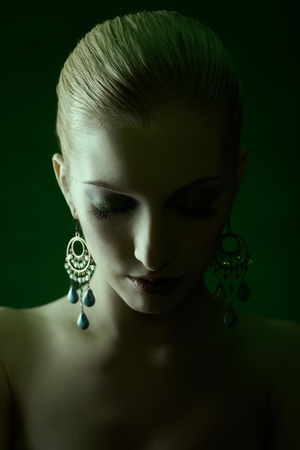 green tinted portrait of beautiful young blonde woman in jewellery with eyes closedの写真素材