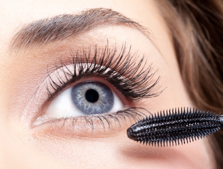 Young beautiful woman applying mascara makeup on eyes by brush