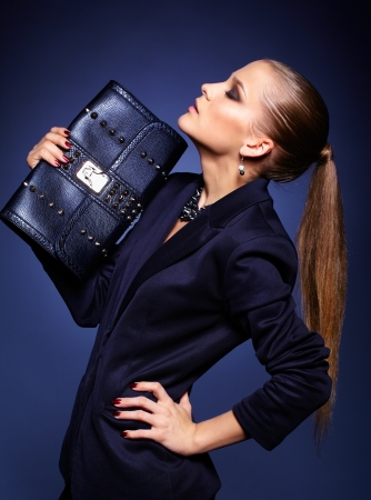 Portrait of beautiful young businesswoman on blue with purse