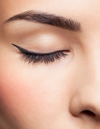 close-up portrait of young beautiful woman's closed eye zone make up with black arrow
