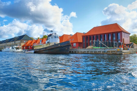 The houses with red roofs and quaysidenear with a moored ship main harbour location in Copenhagen, Denmark.
