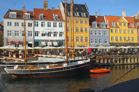 COPENHAGEN, DENMARK - AUGUST 22, 2014: The Nyhavn canal.  Nyhavn is waterfront, canal and entertainment district in Copenhagen.  It is lined by brightly coloured bars, cafes and restaurants