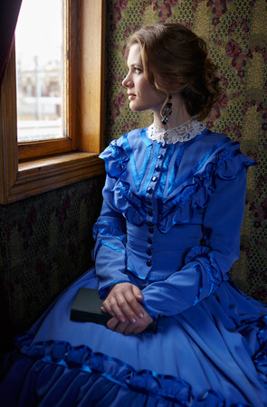 Young woman in blue vintage dress late 19th century sitting with book in coupe of retro railway train and looking out the window