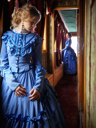 Photo for Young woman in blue vintage dress late 19th century standing near window in corridor of retro railway vehicle - Royalty Free Image
