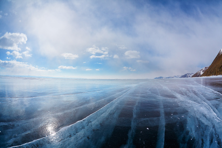 Wide angle shot of winter ice landscape on Siberian lake Baikal with dramatic weather clouds on blue sky background