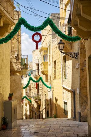 BIRGU, MALTA - JULY 24, 2015: The narrow street of the old capital Vittoriosa decorated for the holiday, Birgu, Malta
