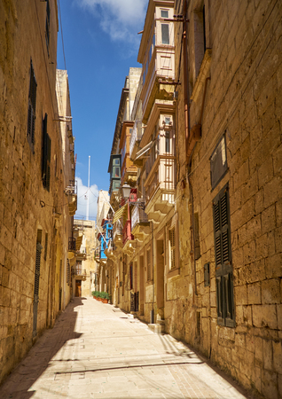 In the sandstone surroundings. The narrow medieval stone paved street and residential houses of Valletta, the capital of Malta.