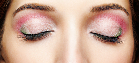 Photo pour Closeup macro shot of human female face with closed eyes and pink - green makeup - image libre de droit