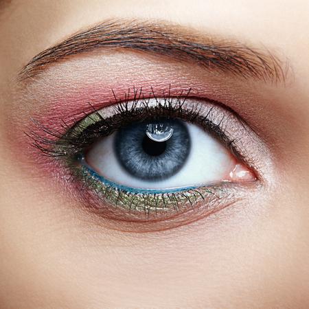 Photo pour Closeup macro image of human female eye with pink and green makeup - image libre de droit