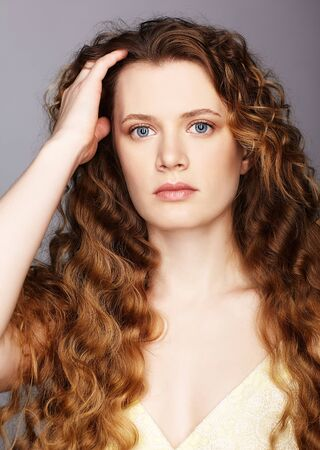 Photo pour Portrait of a young caucasian woman with wavy hair on a gray background. Girl long golden curly hair. - image libre de droit