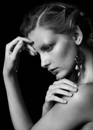 Photo pour Black and white portrait in dark key tone of beautiful young woman touching her shoulder and forehead - image libre de droit