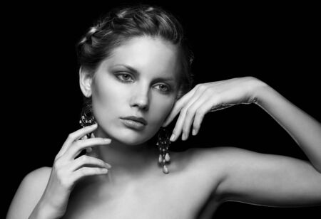 Photo pour Black and white portrait in dark key tone of beautiful young woman  touching face and neck - image libre de droit