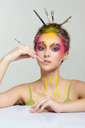 Photo for Portrait of young woman posing at the table with brushes in hair and in her teeth. Unusual female art make-up with paint on brows, hair and around eyes. - Royalty Free Image