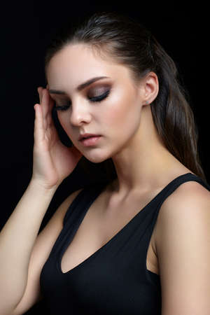 Photo pour Beauty portrait of young woman with hand near face on black background. Brunette girl with evening female makeup and black dess touches face with fingers. - image libre de droit