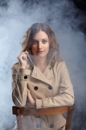 Photo pour Portrait of young beautiful blonde woman is sitting on a chair. Female in beige cloak on smoke background. - image libre de droit