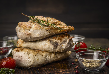 Stack of roast chicken breast with fried seasoning and tomatoes on dark wooden background