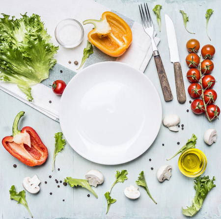 Foto de Ingredients for cooking salad cherry tomatoes, lettuce, peppers, spices and oil  laid out around a white plate on wooden rustic background top view close up - Imagen libre de derechos