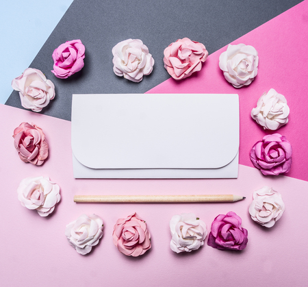Photo pour colorful paper roses on a colorful background, folded around a white envelope decorations for Valentine's Day top view close up place for text - image libre de droit