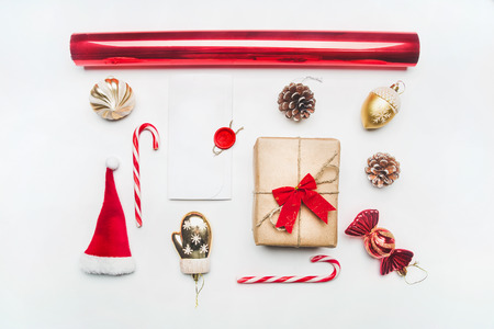 Photo pour Christmas or New Year composition, Santa Claus hat, lollipops, gift in a box with a bow, red packing paper lined up on a white background, top view, flat lay - image libre de droit