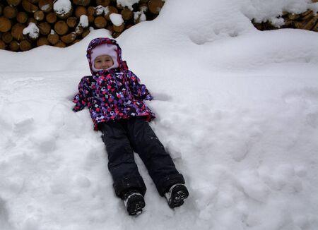 Foto de Bukovel, Ukraine - December 26, 2018. One little girl is having fun on a snow slide and enjoying fresh snow on a beautiful winter day in the mountains. - Imagen libre de derechos