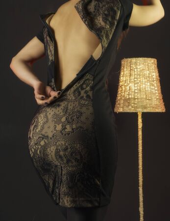 Photo pour Girl takes off a dress in the studio on a black background. Sexual undressing. Rear view. Seduction - image libre de droit