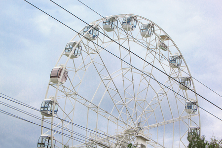Large ferris wheel is spinning in an amusement park.