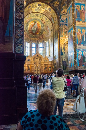 ST. PETERSBURG, RUSSIA - JULY 14, 2016: Interior of Church of the Savior on Spilled Blood. Architectural landmark and monument to Alexander II. Tourists admire the mosaics of the central nave of the temple . Church contains over 7500 square meters of mosa
