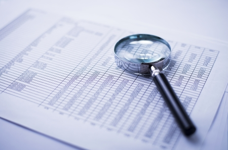 financial statements, documents and magnifier on an office desk