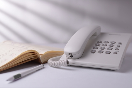 Landline dial up telephone with an open note book or phone directory and pen alongside on a white background with shadow effect