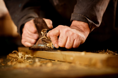 Photo pour Senior man or carpenter doing woodworking planing the surface of a plank of wood in his workshop with a manual plane as he enjoys his creative hobby - image libre de droit