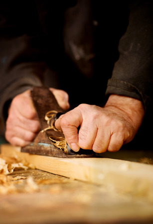 Senior man or carpenter doing woodworking planing the surface of a plank of wood in his workshop with a manual plane as he enjoys his creative hobby