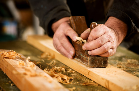 Skilled carpenter using a handheld plane to smooth and level the surface of a plank of hardwood, close up view of his hands, the tool and wood shavings