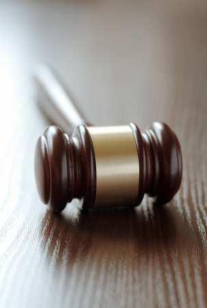 Wooden judges gavel with a central brass band around it lying with the handle facing away on a wooden desk or table with shallow dof conceptual of law enforcement and judgements in court