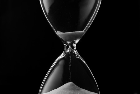 Sand trickling through the bulbs of an hourglass or egg timer measuring the passage of time on a dark background