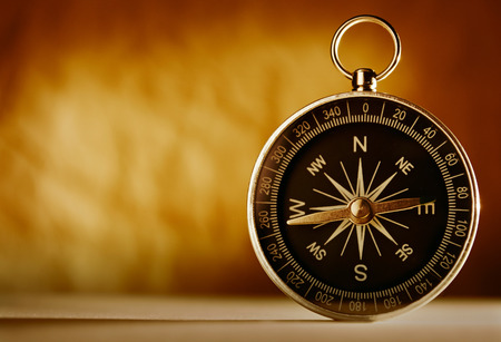 Magnetic compass against an old brown vintage background with a highlight and copyspace in a conceptual image of navigation