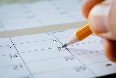 Photo pour Person marking the date of the 15th with a pencil on a blank calendar with date squares as a reminder of an important day or to schedule a meeting or event - image libre de droit
