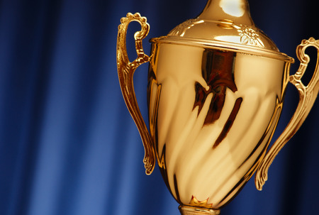 Golden glowing trophy cup on a dark blue background