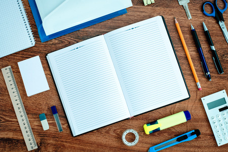 High Angle View of Office or School Supplies Neatly Organized Around Open Note Book with Blank Page on Wooden Desk Top
