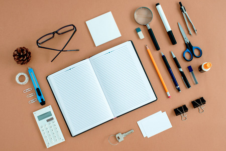 Assortment of Office Supplies Neatly Organized Around Note Book Open to Blank Page on Desk Top Surface