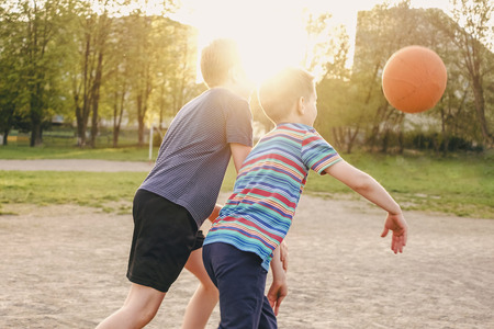 Photo pour Two young boys enjoying a game of basketball challenging each other for the ball backlit by the bright flare of a warm spring sun behind their heads - image libre de droit