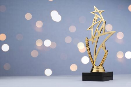 Photo for Modern championship trophy with three gold stars over a laurel wreath for the winner of a sporting event or competition against a bokeh of sparkling lights with copy space - Royalty Free Image