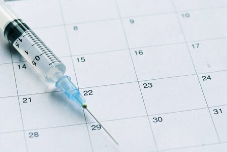 Photo pour Medical syringe with transparent vaccine on white calendar background. Vaccination schedule concept with copy space - image libre de droit