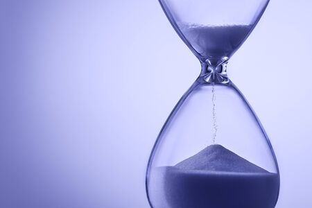 Photo pour Blue toned hourglass with running sand measuring the passage of time in a deadline or countdown concept with copy space - image libre de droit
