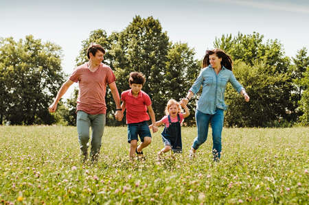 Photo pour Young family with kids running hand in hand through a field or wildflowers in spring or summer approaching the camera in a healthy outdoor lifestyle concept - image libre de droit