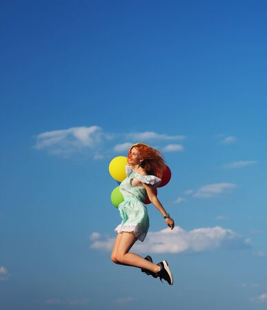 Photo for Young redhead girl with colorful balloons jumping at the blue sky - Royalty Free Image