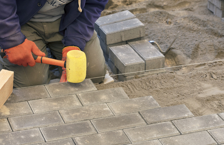 Foto de The worker lay the paving slab with special hammers, leveling it according to the level of the tensioned thread - Imagen libre de derechos