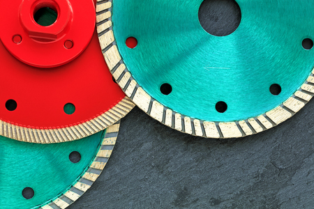 Photo pour Several diamond cutting wheels of red and emerald color are located on top of each other against the background of gray granite close-up. - image libre de droit