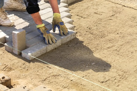 Photo for The worker puts the paving slabs along the stretched thread on the prepared flat sandy ground on the sidewalk. - Royalty Free Image